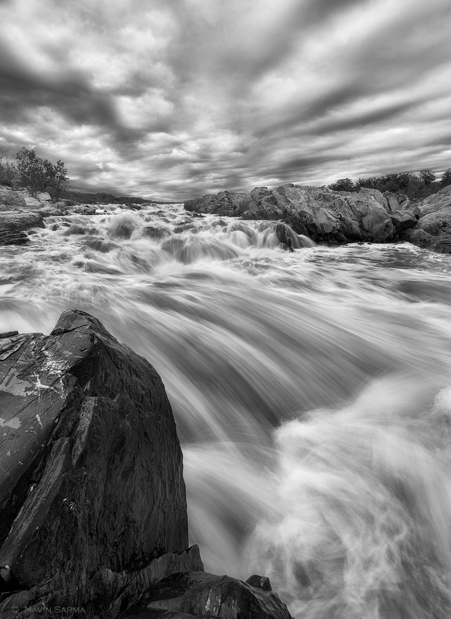 Avenues of sunlit clouds channel across the sky over intense river flow at Great Falls, Virginia.
