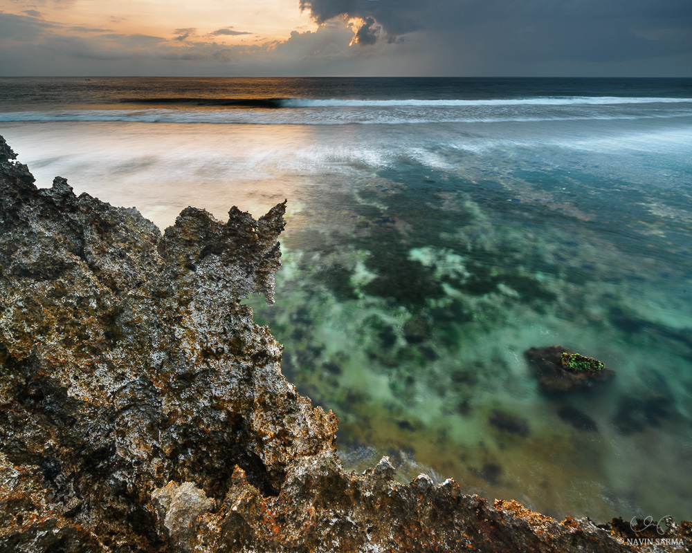 A brilliant sunrise contrasts over limestone cliffs and a shallow lagoon at Nusa Dua, Bali.