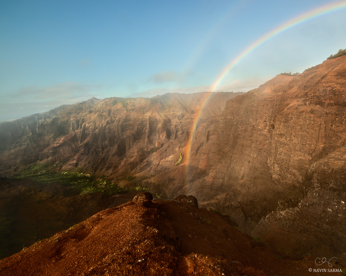 Mist from the valley allows a double rainbow to appear in Waimea Canyon, Hawaii.
