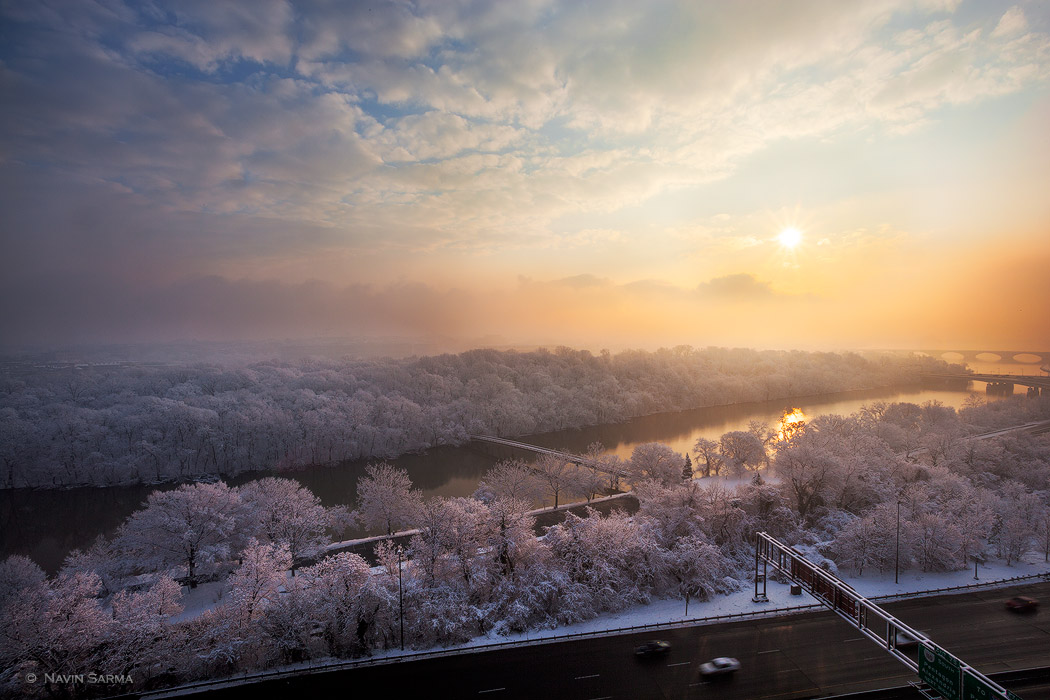 The sun rises over trees plastered with snow at the Potomac River. The Washington Monument is just visible in the distance.
