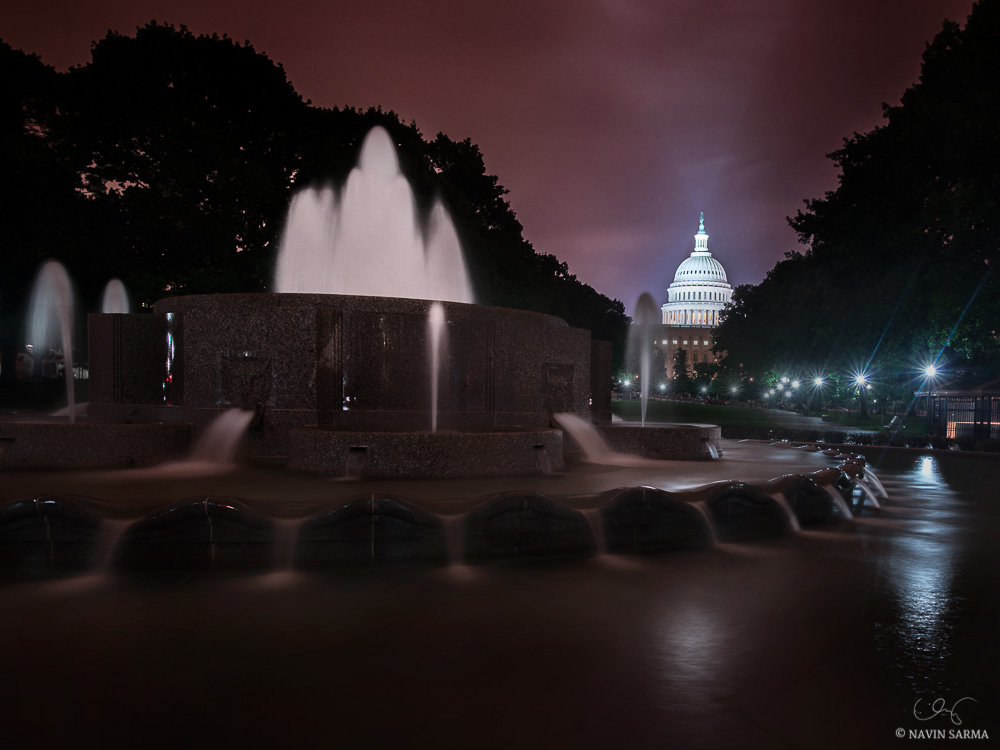A purple sky as night falls over Lower Senate Park fountains and the U.S. Capitol.