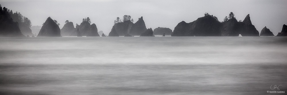 The rising full moon softly illuminates the parade of sea stacks at Point of Arches