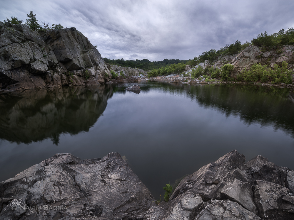 A somber sunset fills blue clouds over a calm section of Great Falls, Maryland