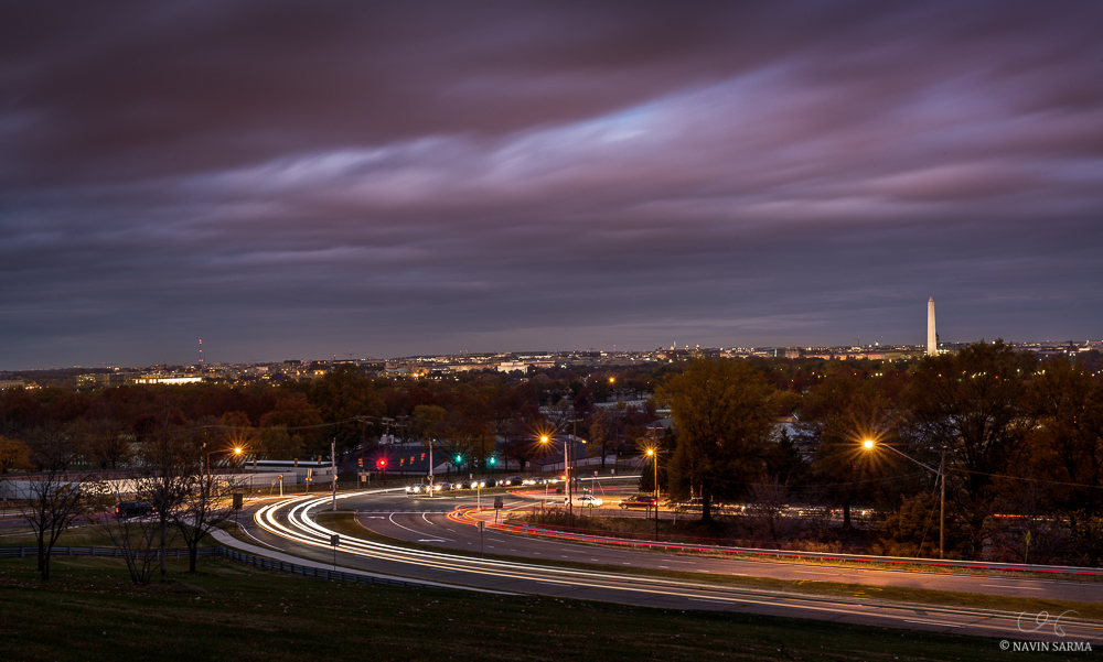 Pink, post-sunset clouds contrast with autumn trees and moving cars from the Air Force Memorial
