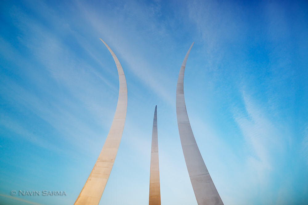 The spires of the Air Force Memorial shine towards the sky at sunset