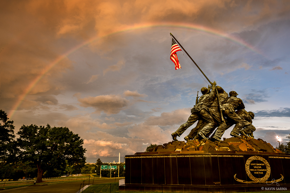 Storms push warm light and a rainbow over the Marine Corps Memorial
