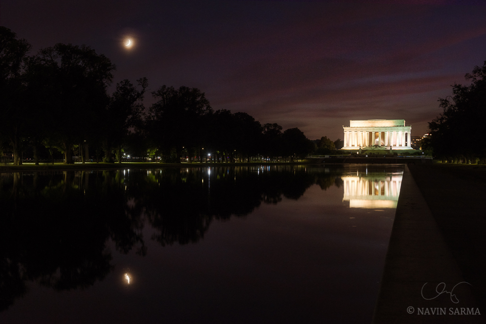 Earthshine illuminates the unexpose moon as it sets over the Lincoln Memorial