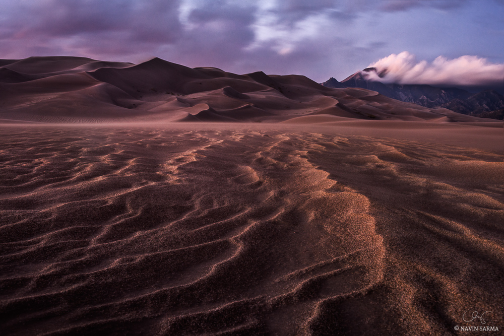 Intense winds turn clouds and ridges of sands into towering dunes against the Sangre De Cristo Mountains of Great Sand Dunes National Park