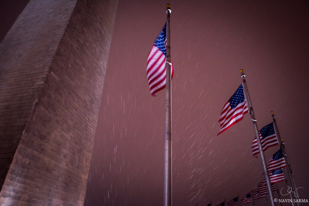 Snow and the surrounding American flags fly towards the Washington Monument during the first night of the 2016 blizzard in Washington DC