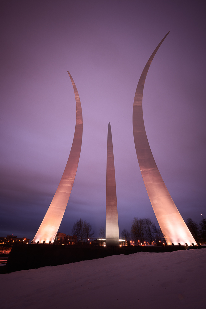 A purple glow from city lights and the sunset as clouds pass by over the Air Force Memorial