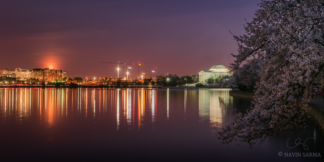 The full moon rises over the Tidal Basin over peaking cherry blossoms