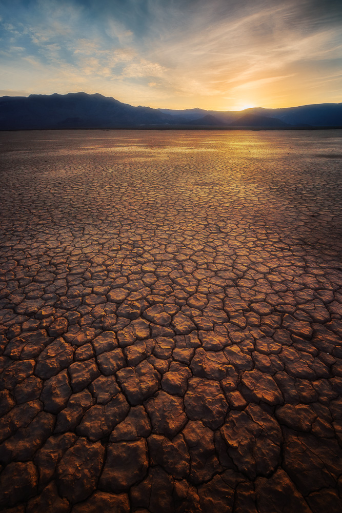 Radiant light shines on cracking mud at Panamint Playa at sunset