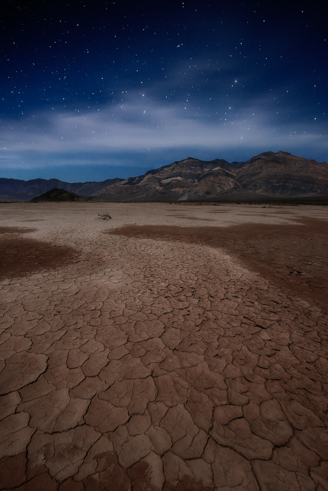 Stars shine brightly over a pathway of cracked mud at Panamint Playa