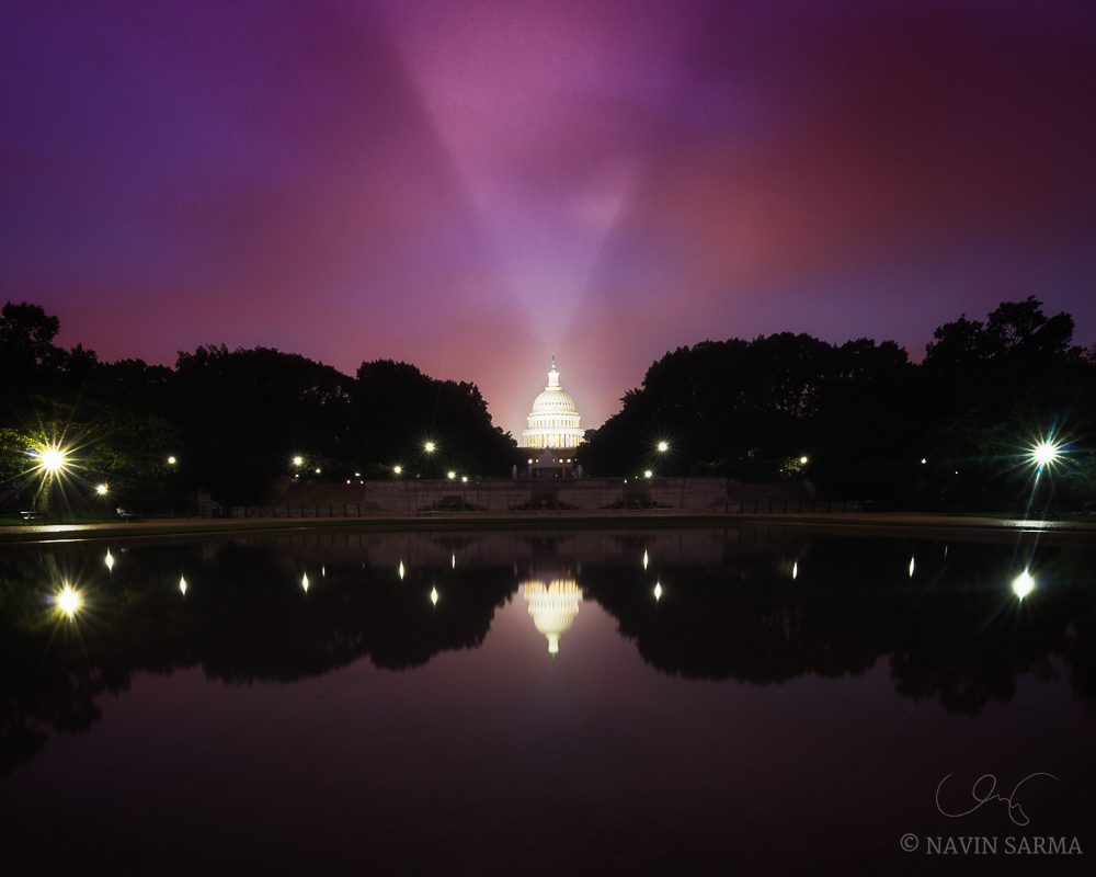 A spotlight illuminates the U.S. Capitol under pink and purple post-sunset clouds
