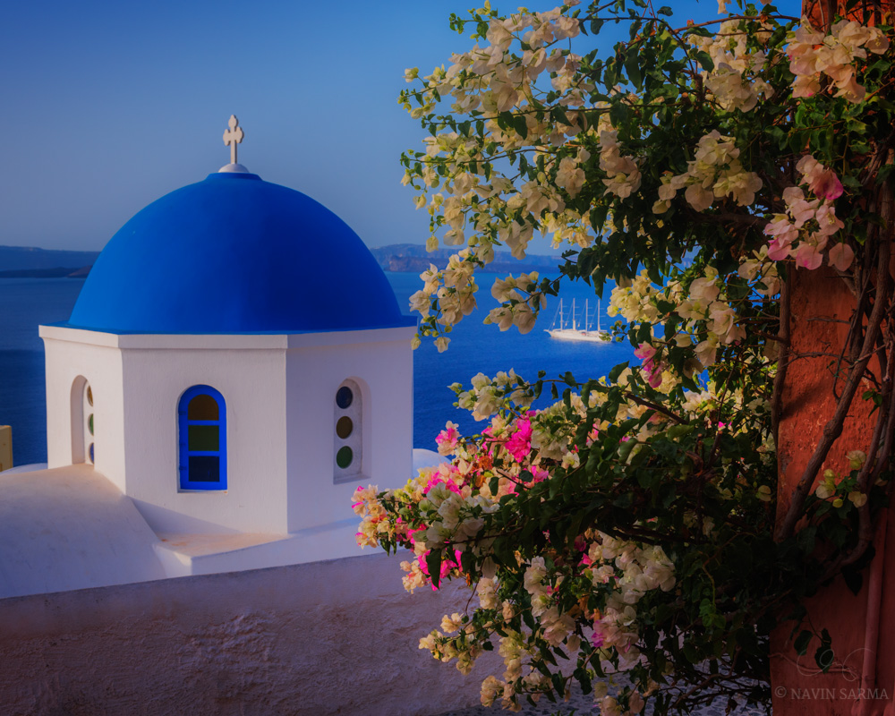 Flowers adorn the edges of the walls near a church in Santorini