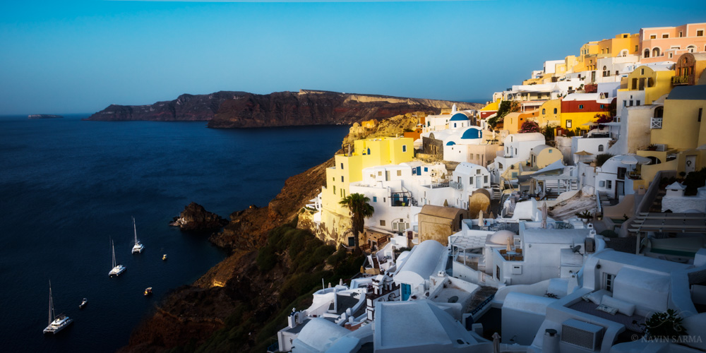 A panoramic of early light streaming onto the cliffs of Oia, Santorini