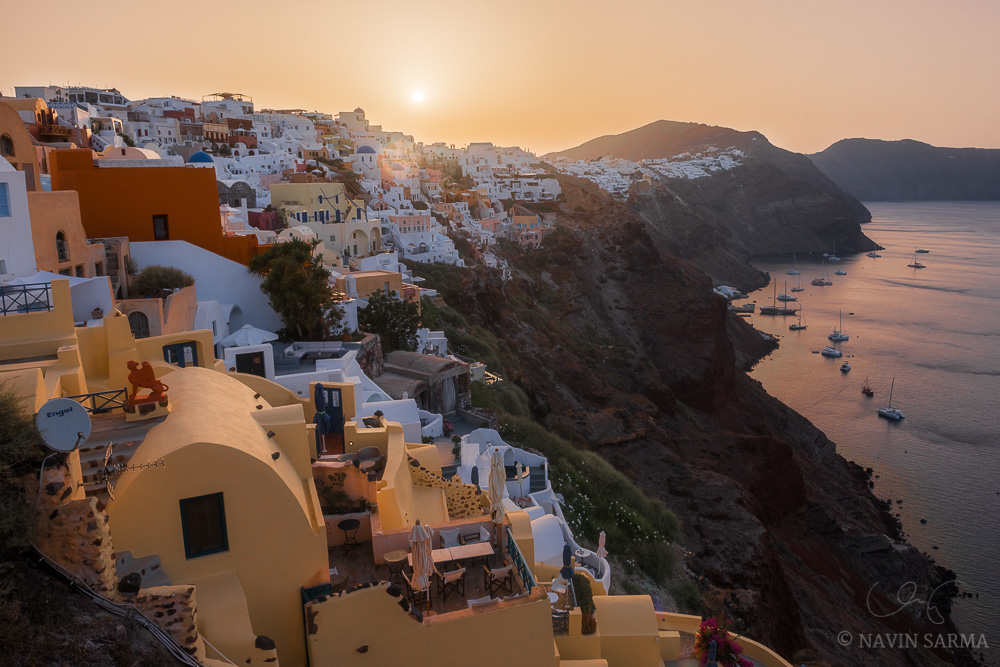 The sun rises over a cloudless landscape from Oia in Santorini, Greece