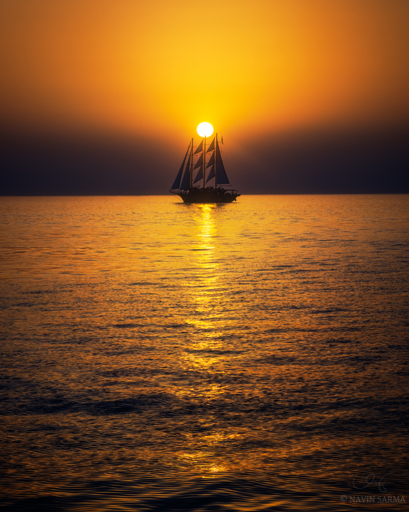 A sailboat full of people witnessing the cloudless sunset in Santorini