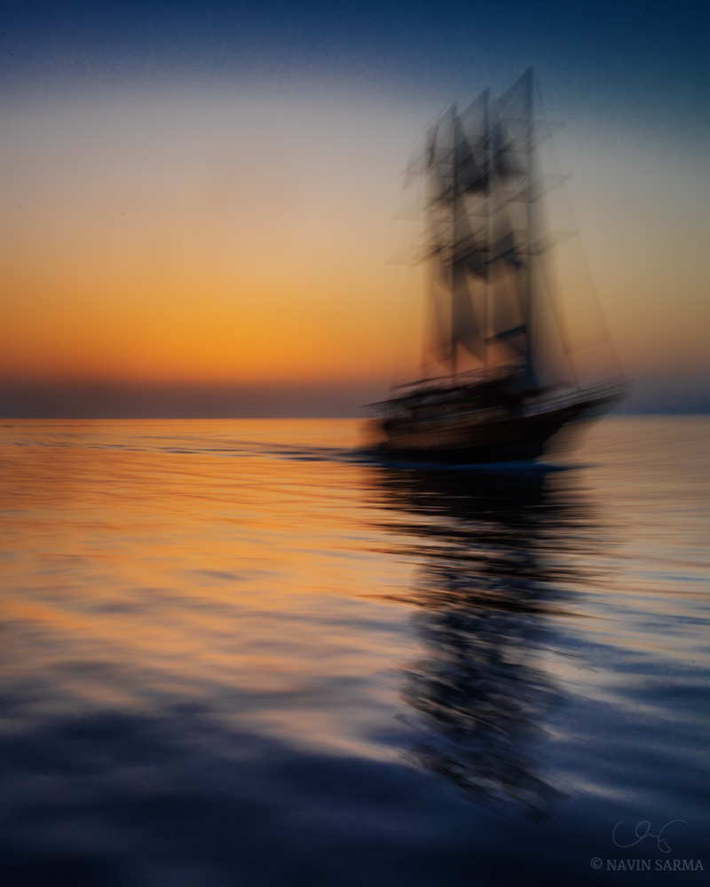 A pan motion of a speeding sailboat just after sunset in Santorini