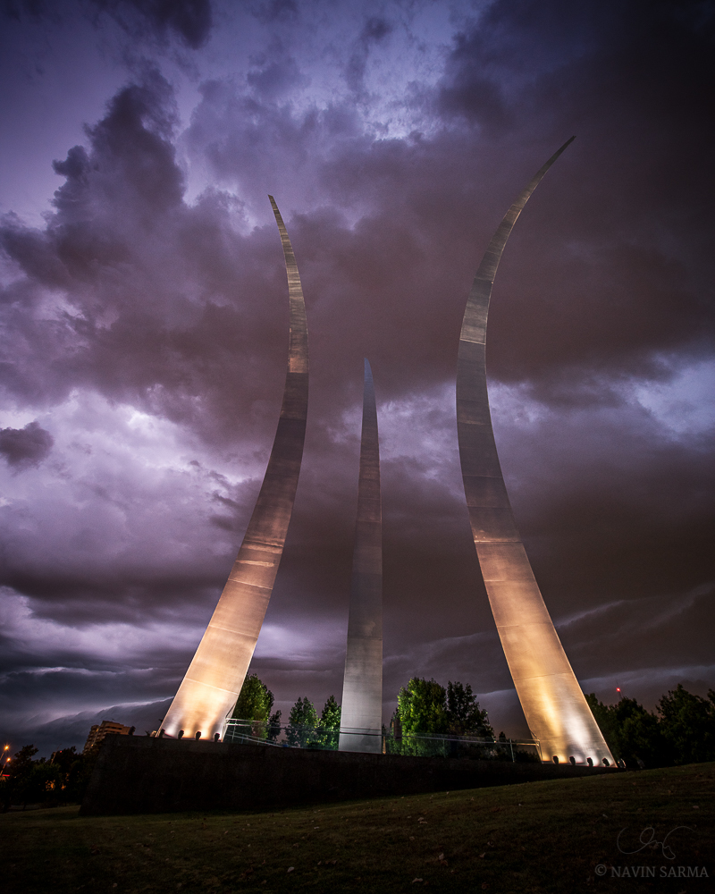 Lightning strikes behind dark clouds, revealing their shape and color over the Air Force Memorial