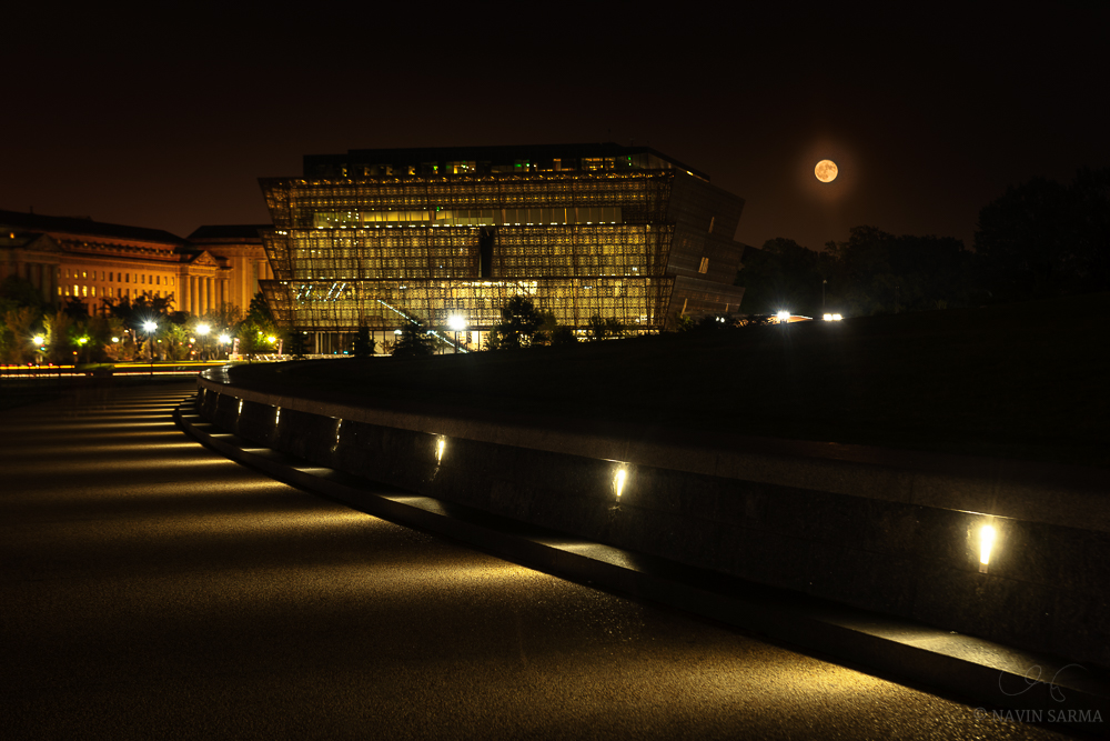 The full moon rises over the African American History Museum in Washington DC