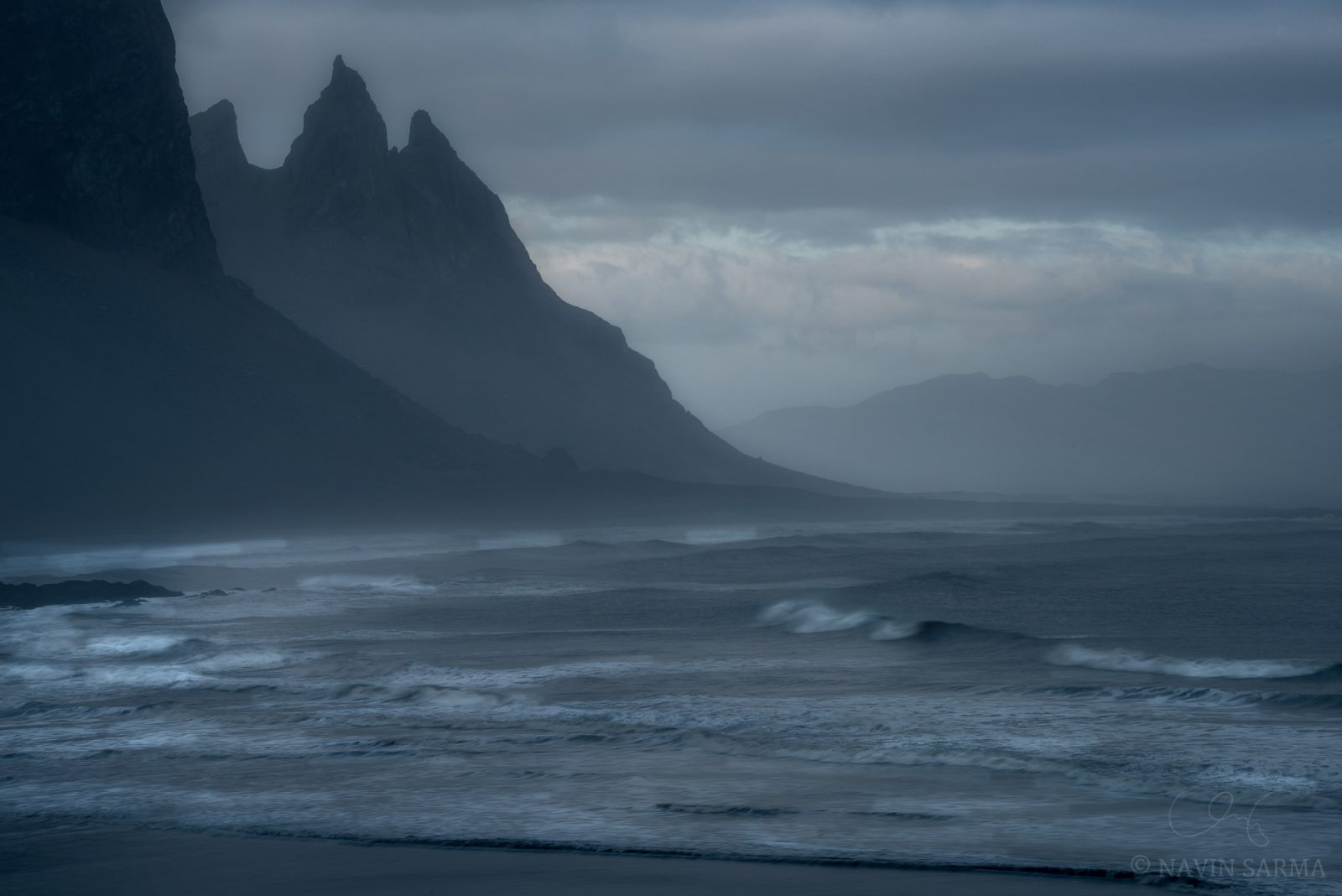 Peaks and waves rise in the distance at Vesturhorn mountain