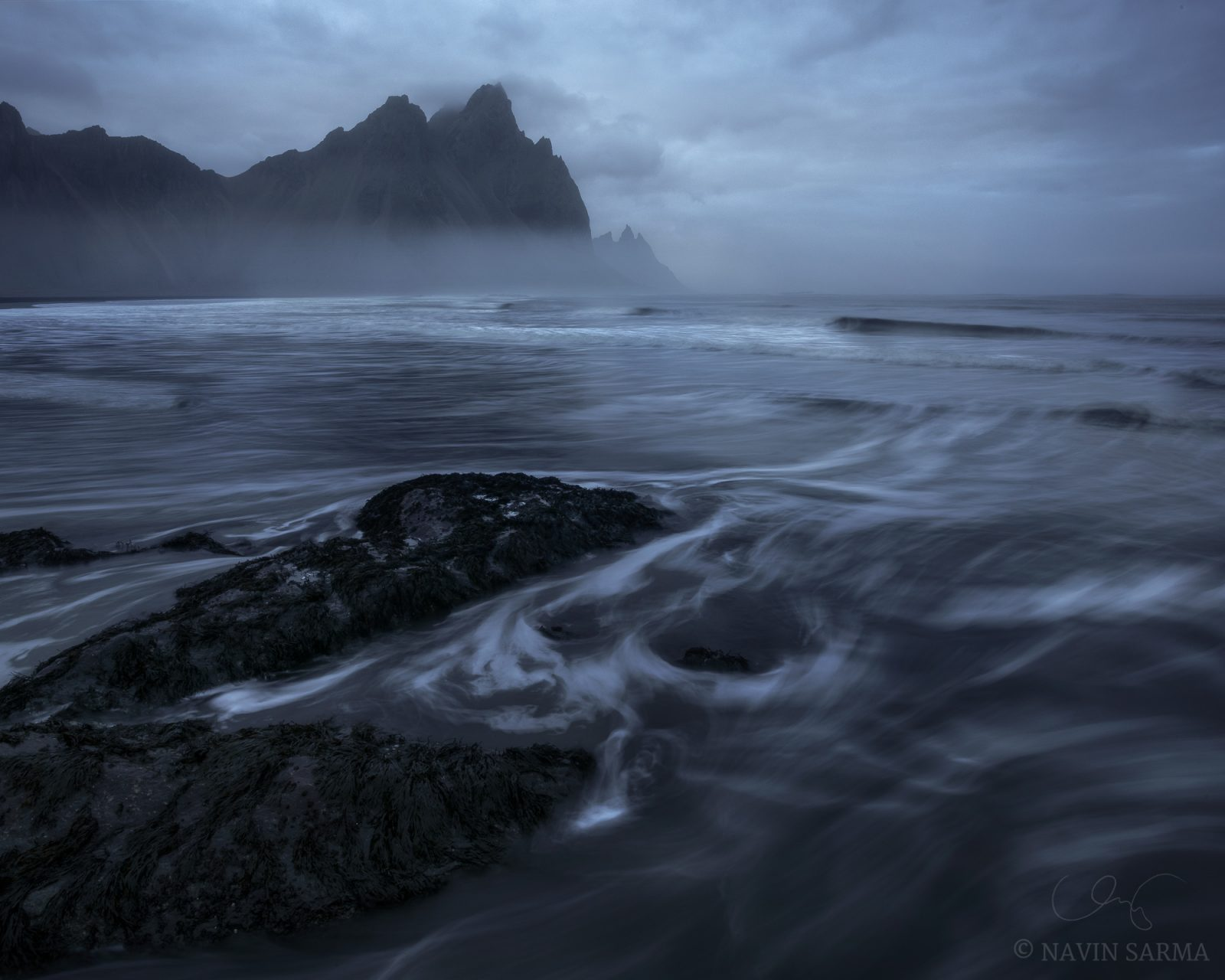 As the tide rises up the beach the sun sets creating a moody scene at Vesturhorn mountain