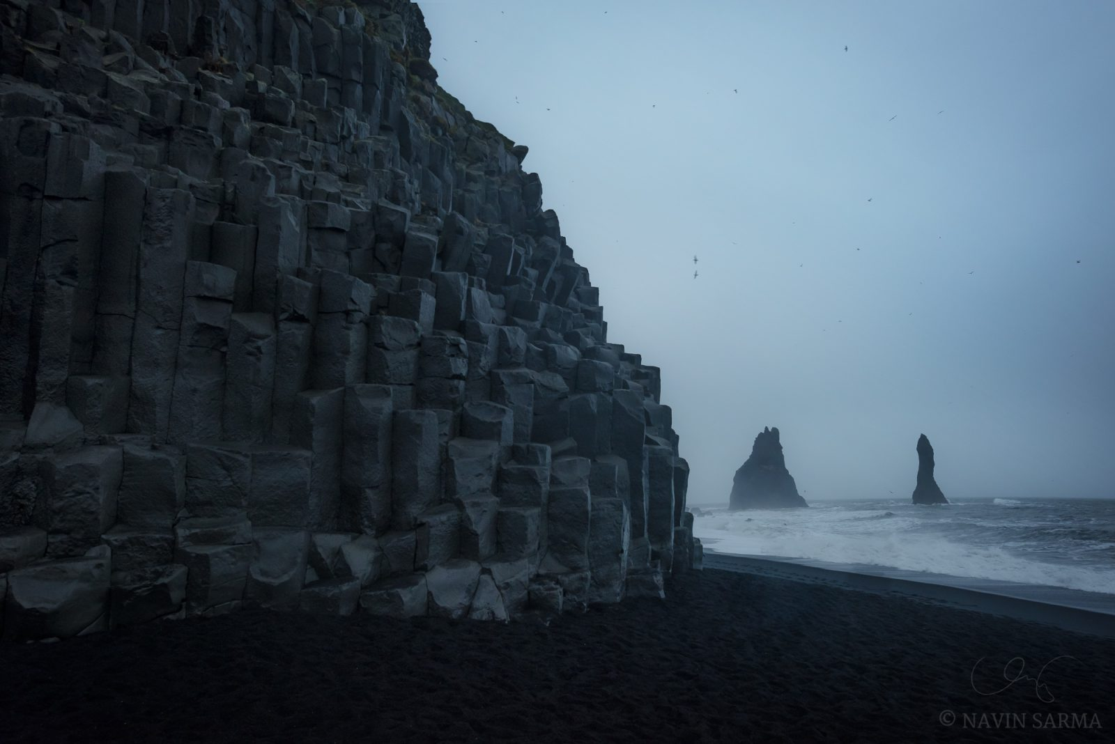 Basalt columns, soaring birds, crashing waves, and dramatic seastacks make the signature of Reynisfjara beach in Vik