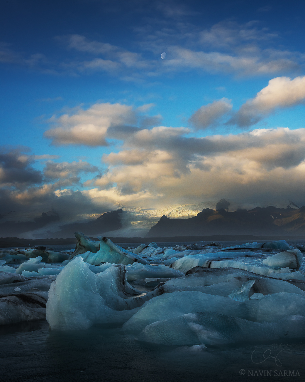 The moon peaks through clouds at sunrise at Jökulsárlón