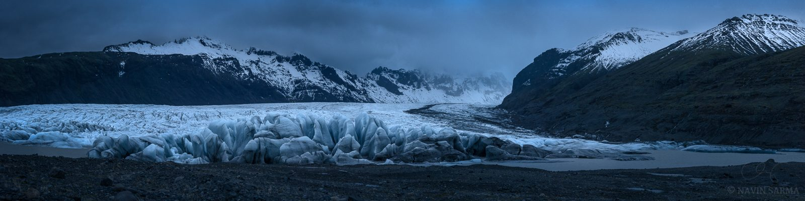 Massive shapes at the edge of the Vatnajökull glacier trail far into the valley during a somber sunset