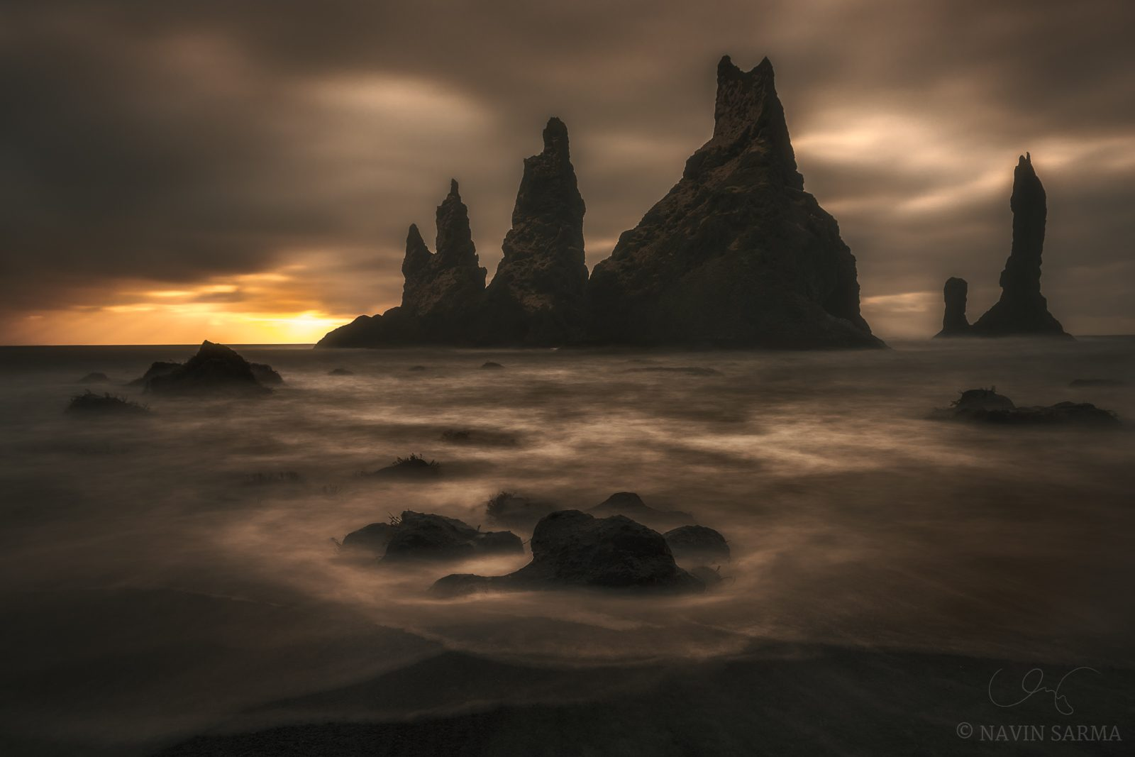 Enter Darkness - A long exposure at sunrise creates a moody scene upon full view of the impressive sea stacks at Reynisfjara beach