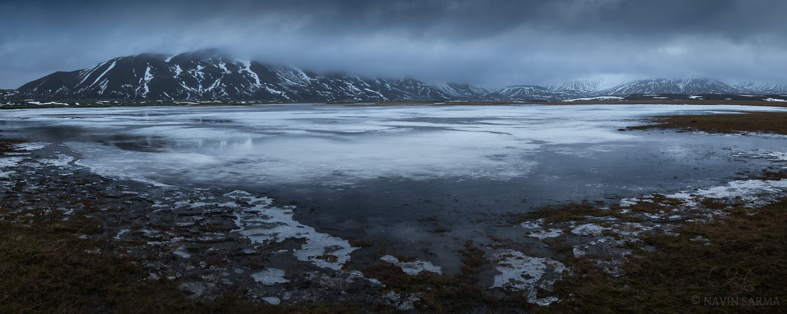 Moody Mountaintops - Overcast skies cover the peeks of massive mountains above a frozen lake in east Iceland