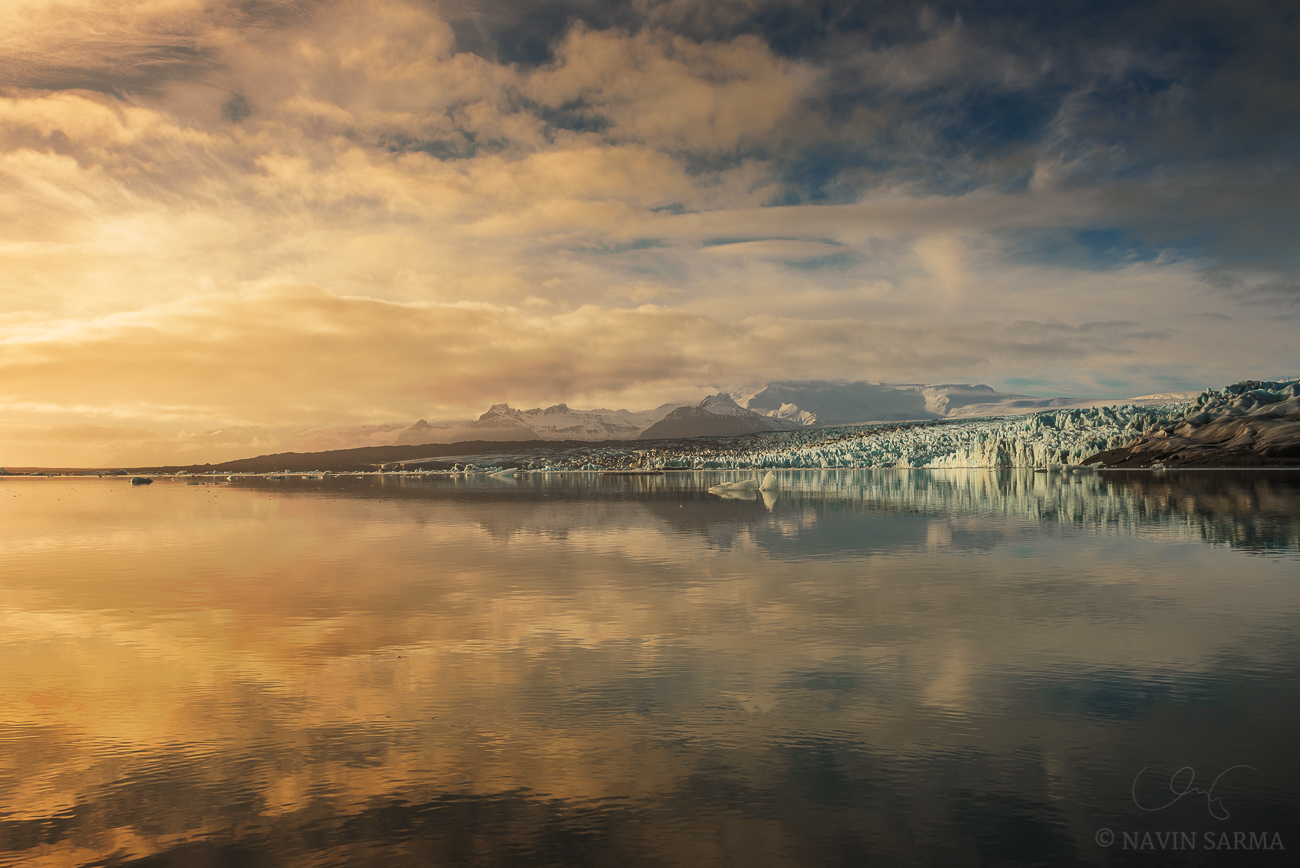 Glacier Lake Reflection - The still glacier lagoon reflects light and the distant glacier and mountains at Vatnajökull