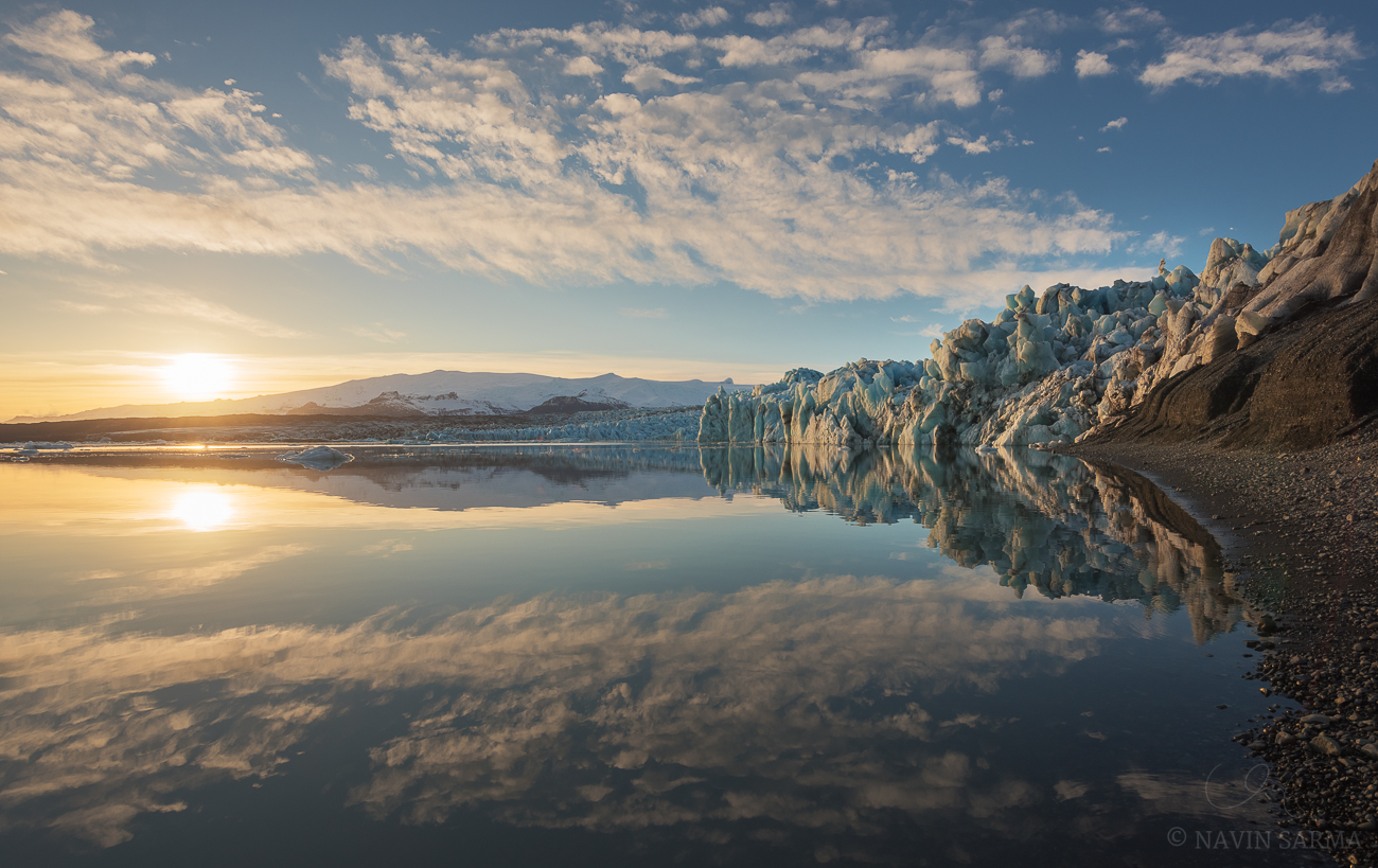 Glass and Ice - Clouds and the sun reflect in the calm glacier lagoon at sunset in front of the Vatnajökull glacier