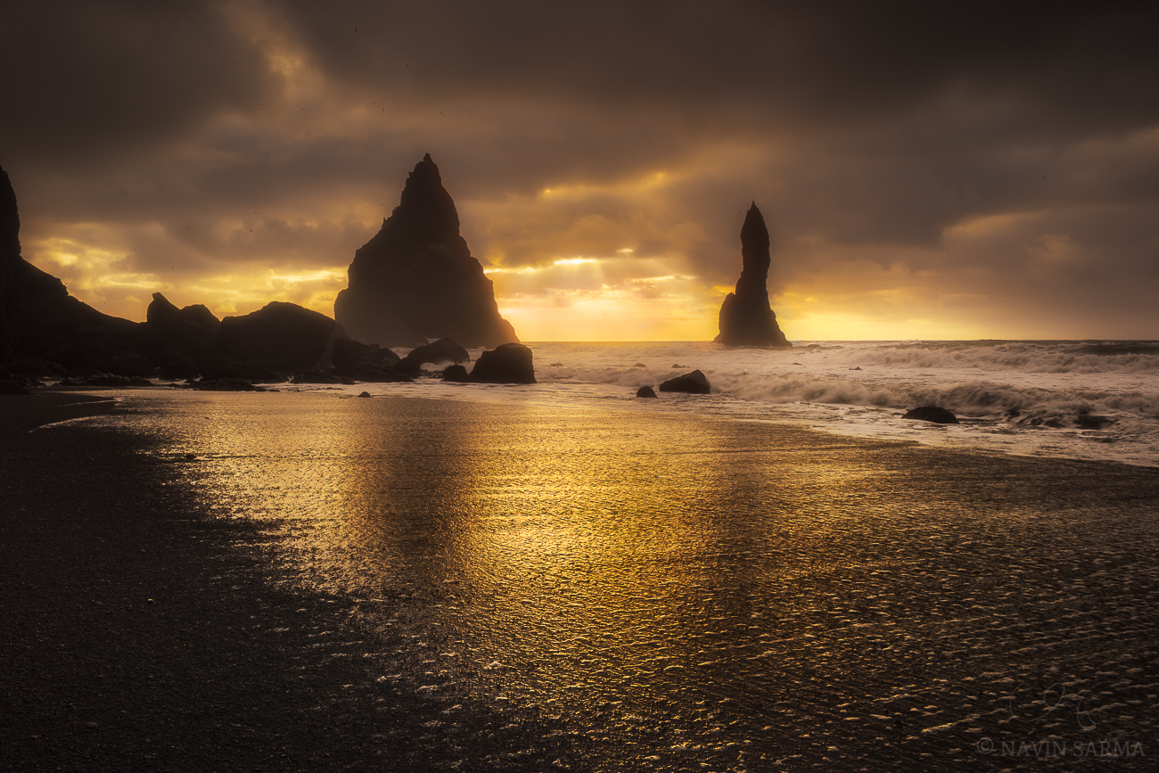 Shimmer Beach - Sunlight reflects the shadows of Vik's sea stacks and bright sparkles of shimmering volcanic rocks that make up the black beach