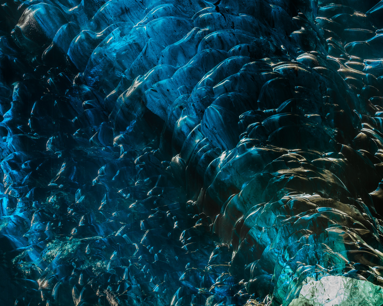 Stained Glass - Light streams through cyan ice that resembles stained glass in a massive ice cave under the Vatnajökull glacier