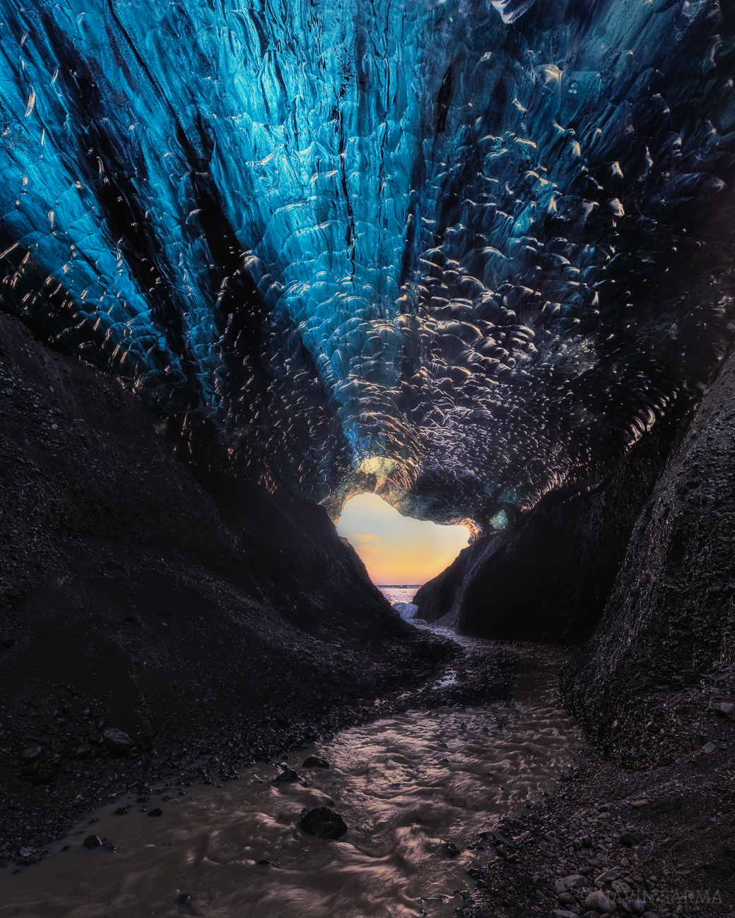 Under the Cave - Melting water rushes out from the glacier into the lagoon under a translucent ceiling of glacier ice