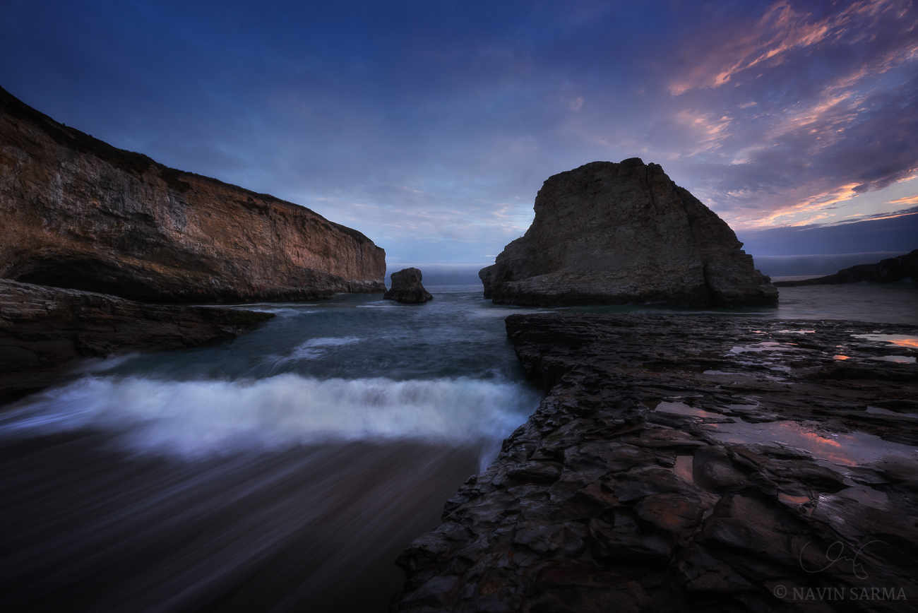 Intense waves crash up the coast at sunset at Shark Fin Cove