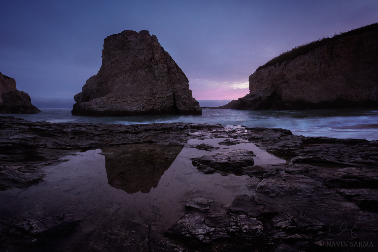 The namesake sea stack of Shark Fin Cove reflects in tide pools at the shore at sunset