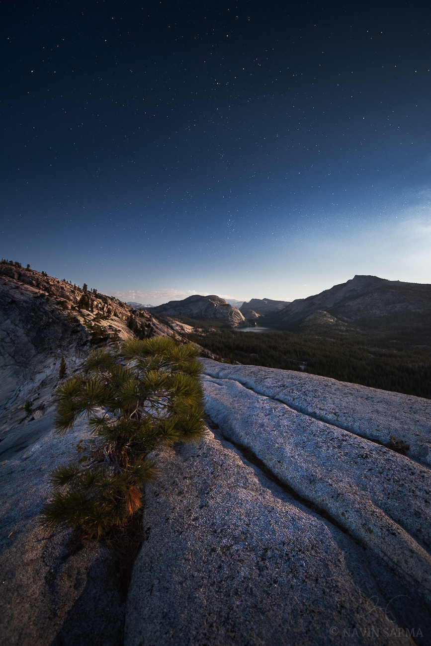 The full moon shines light on granite under the blue, early night sky filled with stars