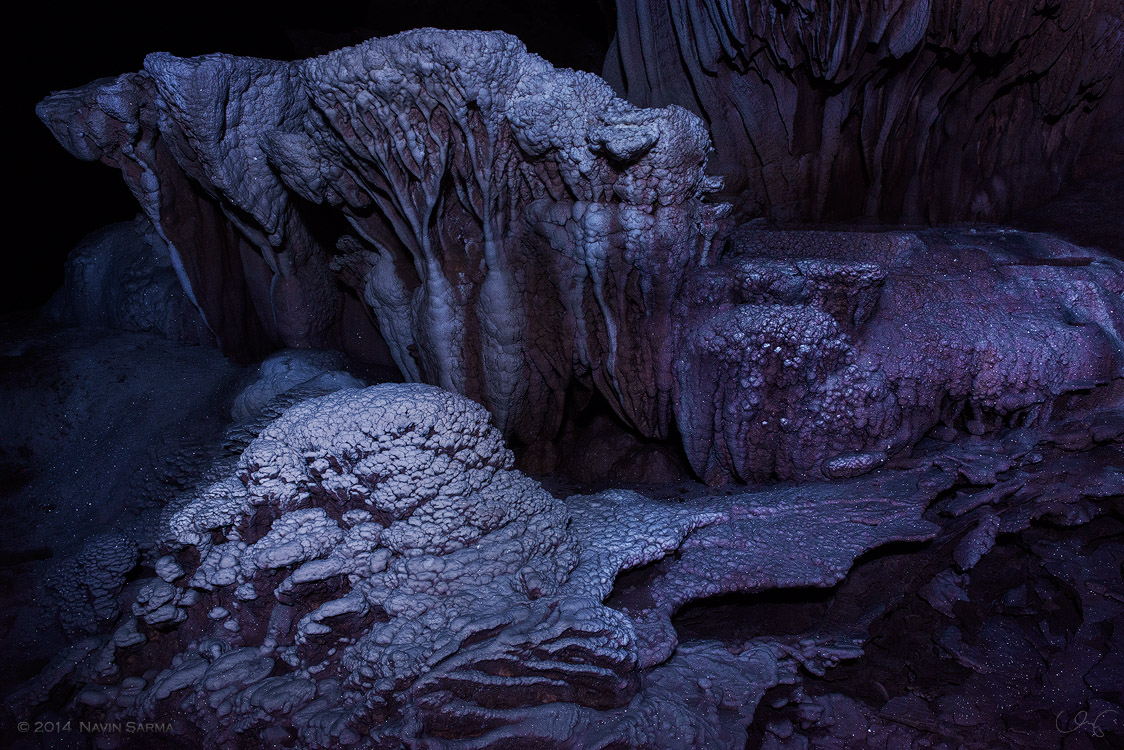 Calcite crystals shimmer over stalagmite formations like fresh snowfall on rocks.