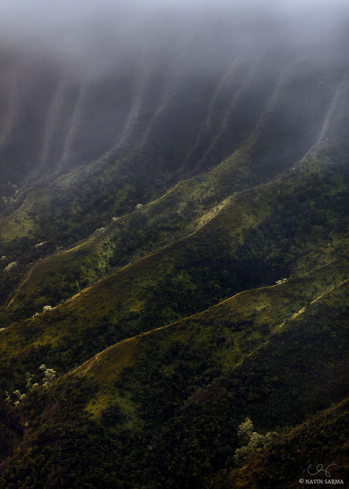 Mist scatters the cool morning light amongst the cliff edges of the Kalalau Valley