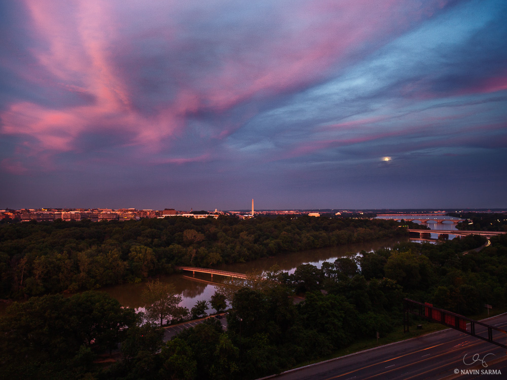 Pink clouds highlighted from the setting sun contrast with the rising moon over the Potomac River of Washington DC