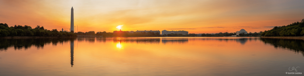 The sun rises between the Washignton Monument and Jefferson Memorial