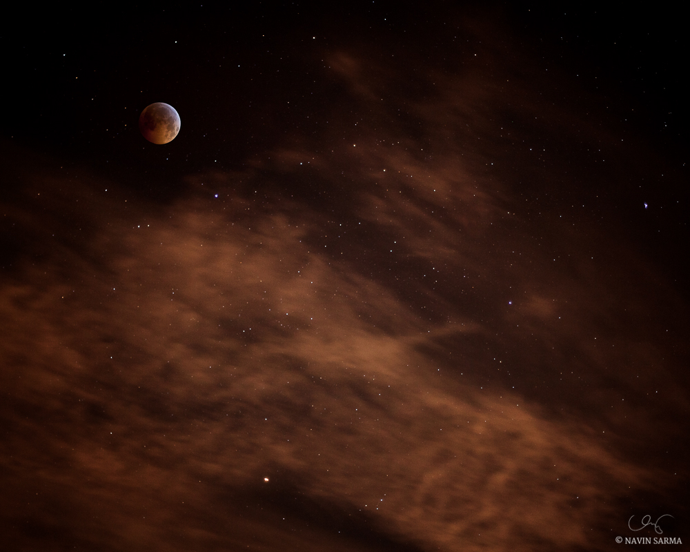 The total lunar eclipse of 2010 in a photo composite. The moon was shot with a zoom lens at 200mm, while the clouds and stars were shot at 50mm.