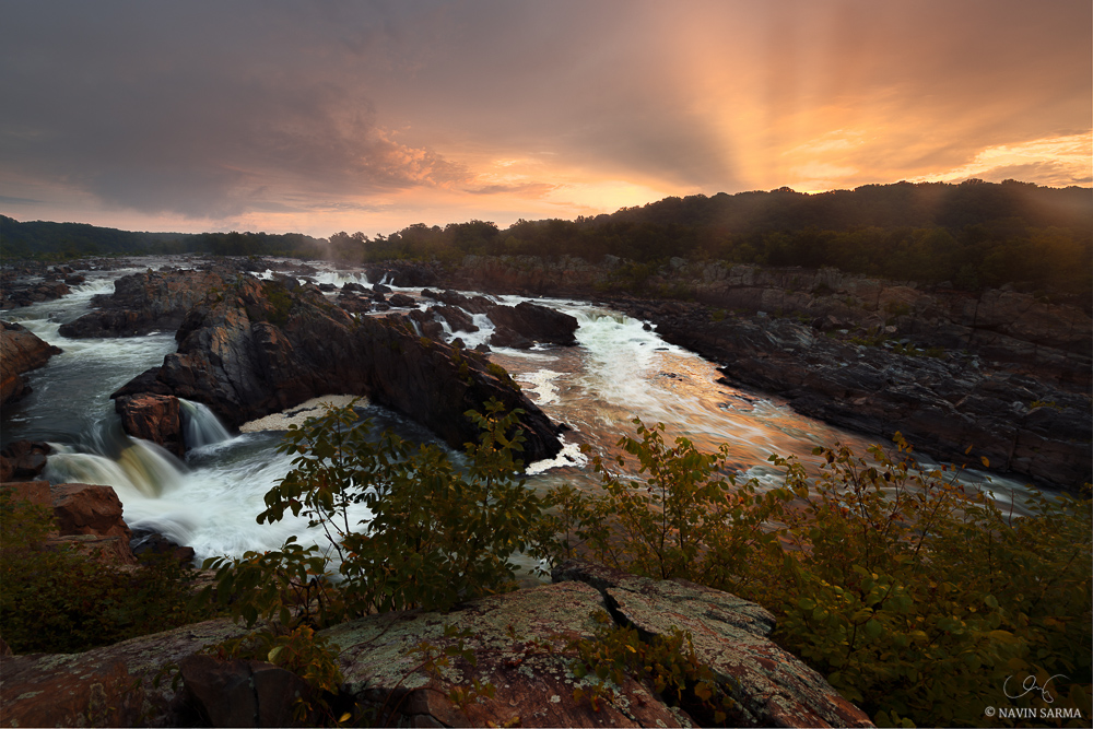 A wide view of a golden sunrise complete with crepusculars (god rays) during summer at Great Falls National Park