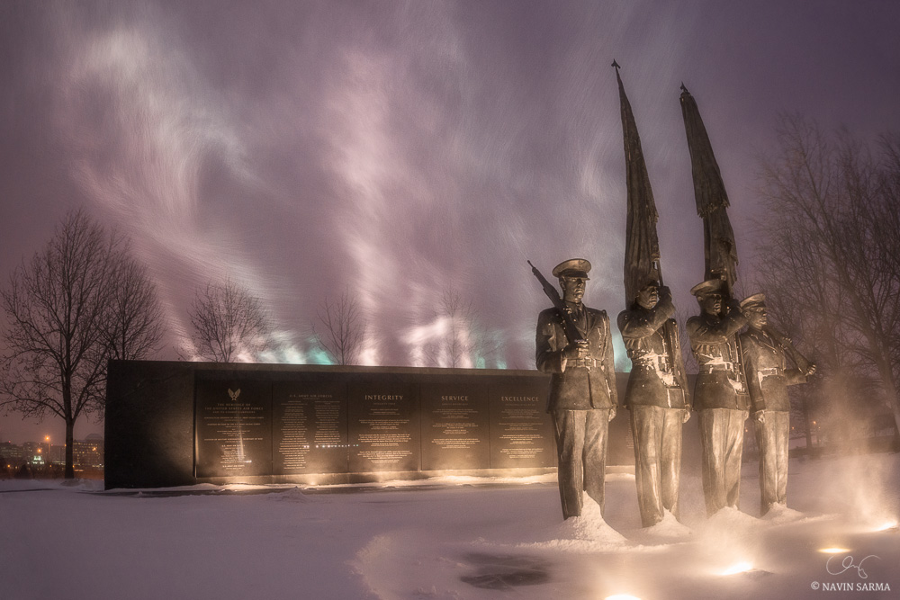 Snow and wind mix in with purple city glow at sunset at the Air Force Memorial