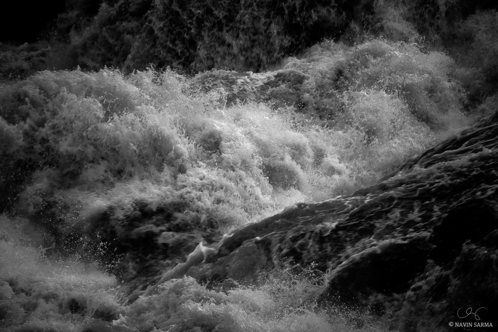 Sun peeks through thunderclouds between rainfall on the violent rapids of Great Falls
