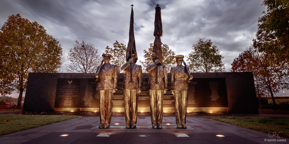 The Honor Guard shines gold as late sunset light mixes with the glow of lighting beneath the Memorial.