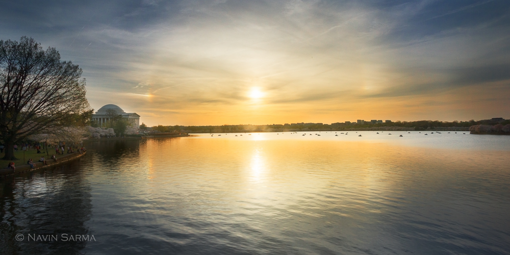 A beautiful sunset at the Tidal Basin in front of many paddle boaters and a sun halo reflected in the water